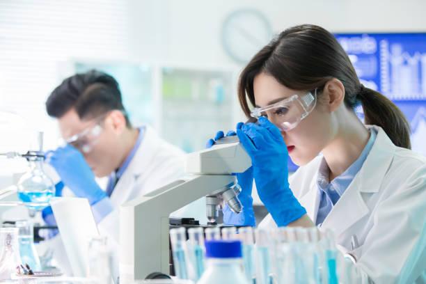 アジアの科学者使用顕微鏡 - 医療処置 ストックフォトと画像