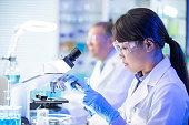 アジアの科学者使用顕微鏡