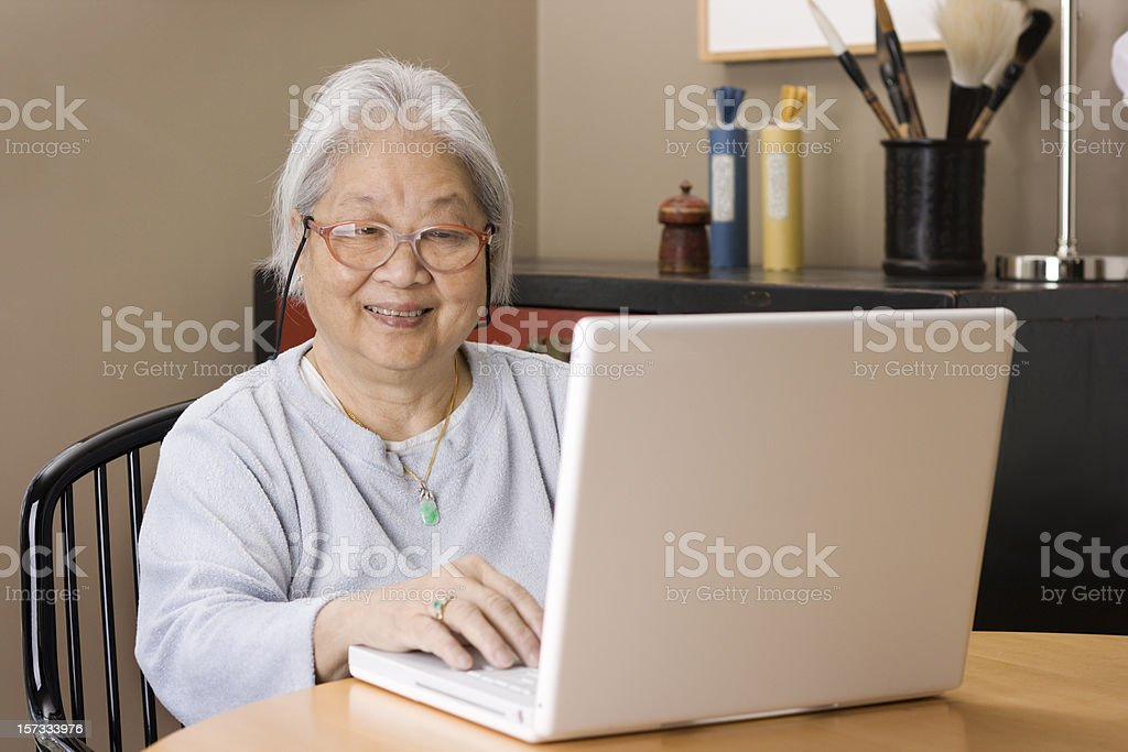 Asian Senior Adult Woman Using Laptop Computer, Happy and Smiling royalty-free stock photo