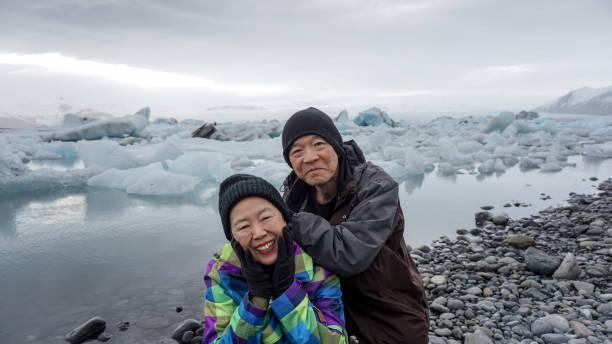 Asian senior couple fun trip in Iceland, majestic glacier lagoon landscape stock photo