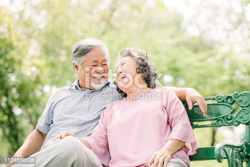 An elderly woman hugs her husband sitting on the bench in the park looking at camera