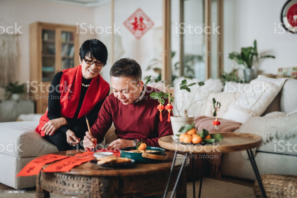 Asian senior couple practising Chinese calligraphy for Chinese New Year Fai Chun (Auspicious Messages) by writing it on a piece of red paper Asian senior couple practising Chinese calligraphy for Chinese New Year Fai Chun (Auspicious Messages) by writing it on a piece of red paper Active Seniors Stock Photo