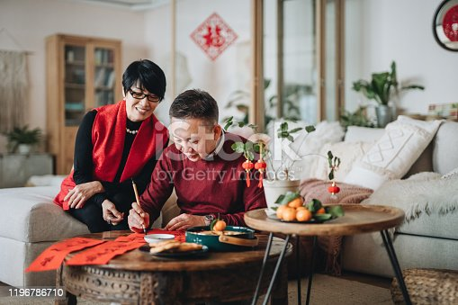 Asian senior couple practising Chinese calligraphy for Chinese New Year Fai Chun (Auspicious Messages) by writing it on a piece of red paper