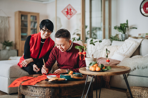 Asian Senior Couple Practising Chinese Calligraphy For Chinese New Year Fai Chun By Writing It On A Piece Of Red Paper Stock Photo - Download Image Now