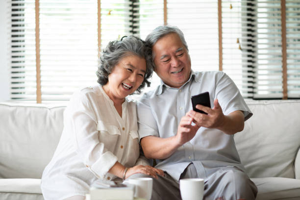 Pareja de la tercera edad asiática usando el teléfono celular. - foto de stock