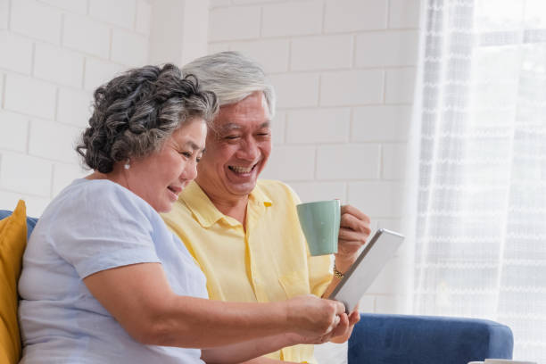 Asian senior couple using table compute and drink coffee sitting at sofa in living room at home.senior with technology lfiestyle.aging at home concept. Asian senior couple using table compute and drink coffee sitting at sofa in living room at home.senior with technology lfiestyle.aging at home concept. medicare stock pictures, royalty-free photos & images