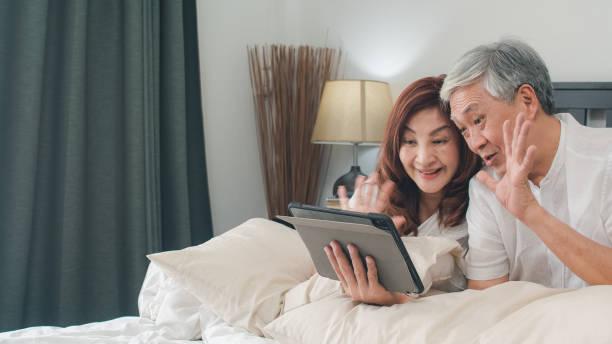 Asiatische Senior-Paar mit Tablet zu Hause. Asiatische Senior chinesische Großeltern, Video-Anruf im Gespräch mit Familie Enkelkinder, während auf dem Bett im Schlafzimmer zu Hause im Morgen Konzept liegen. – Foto