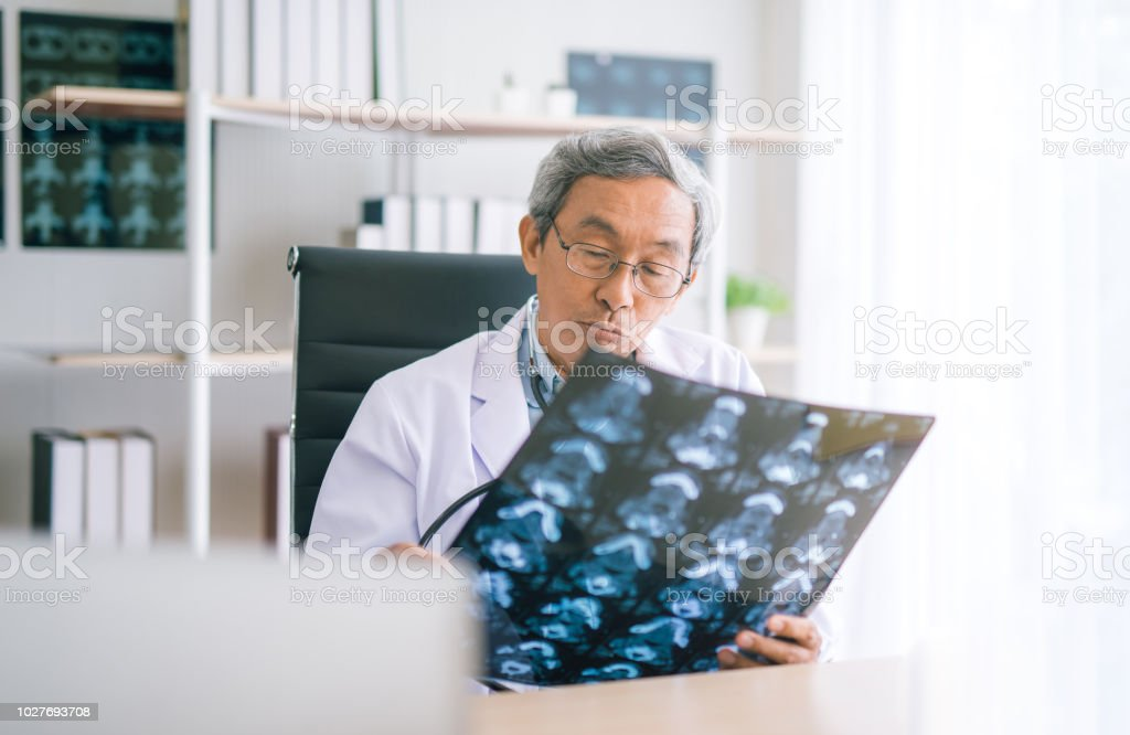 Asian Senior Doctor looking chest x-ray film in hospital. stock photo