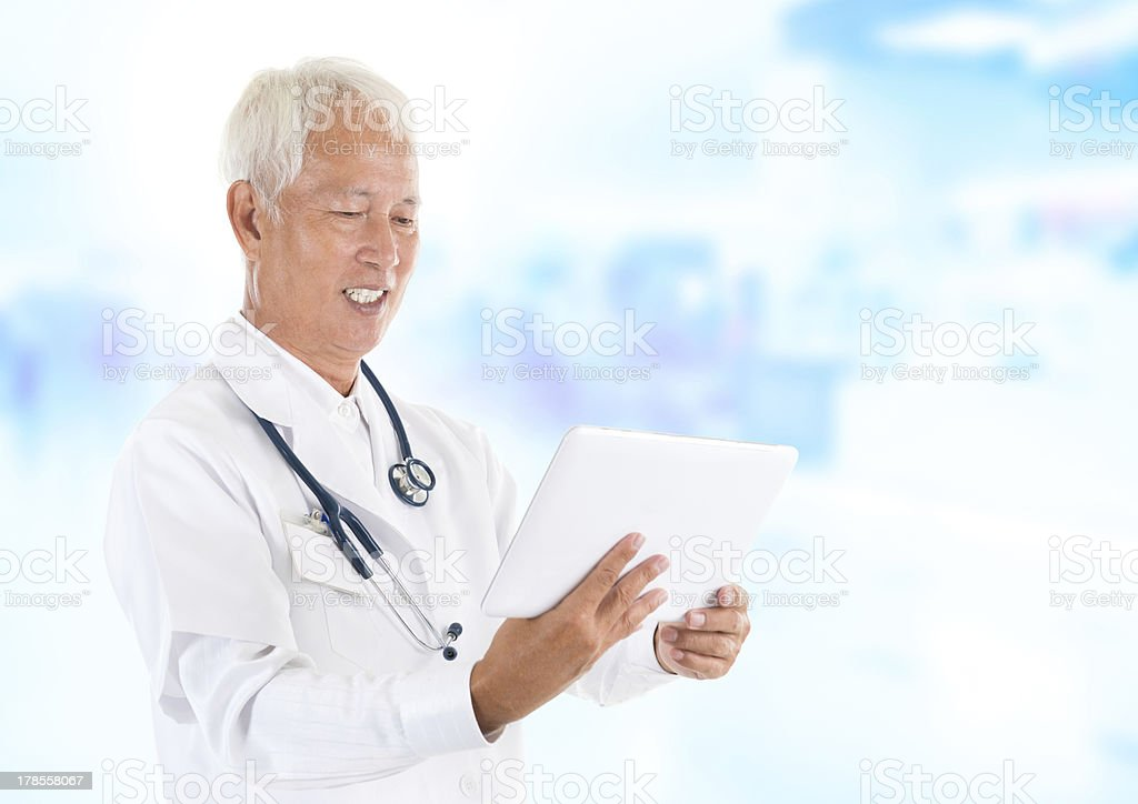 Asian senior doctor using tablet-pc royalty-free stock photo