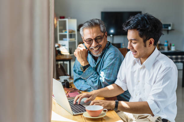 asian senior father and his adult son using laptop computer while sitting at home - filhos adultos imagens e fotografias de stock