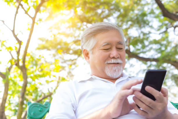 Asian senior man chatting with family by using smart phone, video call, internet wireless at park. His family stay at overseas. Mature guy get happy when chatting with them. Relieve loneliness stock photo