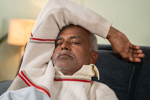 Asian senior man having nice sleep on bed at home - concept of better sleep or nap and healthy lifestyle
