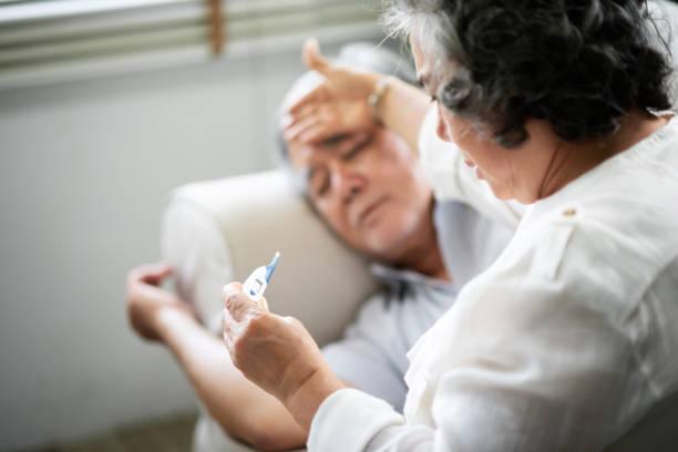 아시아 수석 남자가 그의 아내를 개최 하 고 온도계를 찾고 있는 동안 소파에 누워 있다. - 온도 뉴스 사진 이미지