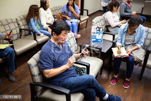 An Asian senior man uses his smartphone to pass the time while waiting in a medical clinic's waiting room.