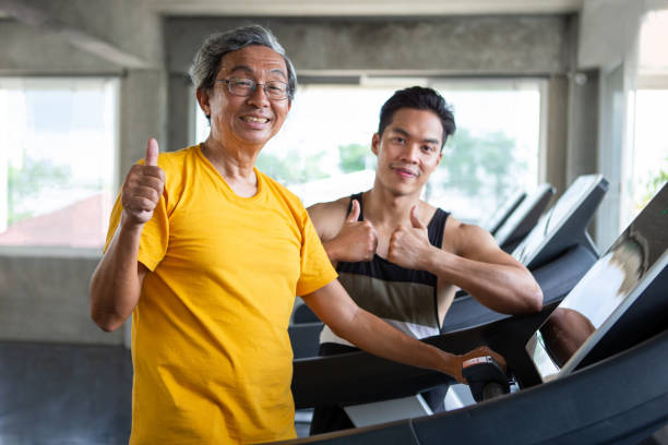 asian senior man walking exercise on treadmill with personal trainer workout in fitness gym and show thumbs up . sport trainnig , retired , older , mature, elderly , smiling .rehab - runner rehab gym foto e immagini stock