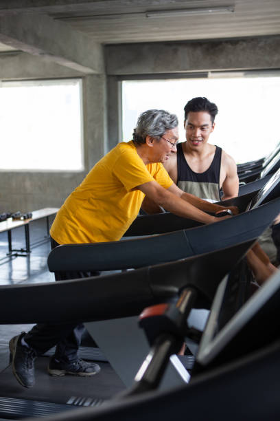 asian senior man walking exercise on treadmill with personal trainer workout in fitness gym . sport trainnig , retired , older , mature, elderly , smiling .rehab - runner rehab gym foto e immagini stock