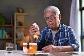 Asian senior man  with his medicine bottles