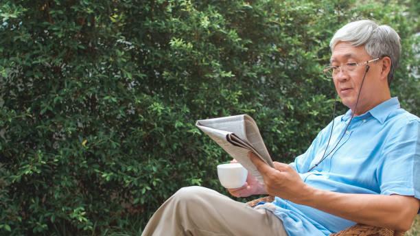 Asiatische Senioren entspannen zu Hause. Asiatische Senior chinesischen männlichen genießen Ruhezeit tragen Gläser lesen Zeitung und trinken Kaffee, während im Garten zu Hause im Morgen Konzept liegen. – Foto