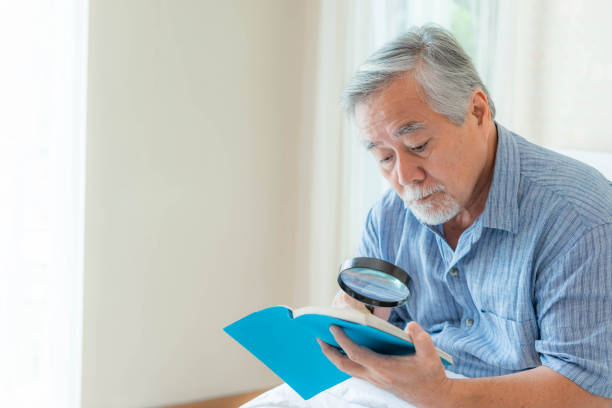 Asian senior old man longsighted , farsighted , reading a book with a magnifying glass on white bedroom - lifestyle senior male have farsightedness problems concept stock photo