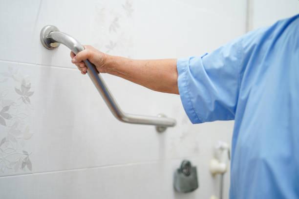 aziatische senior of ouderen oude dame vrouw patiënt gebruik toilet badkamer handvat veiligheid in verpleging ziekenhuis ward: gezond sterk medisch concept. - veiligheidshek stockfoto's en -beelden