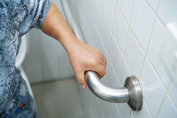 asya yaşlı veya yaşlı yaşlı kadın kadın hasta bakım hastanesi koğuşunda tuvalet banyo kolu güvenlik kullanın: sağlıklı güçlü tıbbi kavram. - tutamak üretilmiş nesne stok fotoğraflar ve resimler