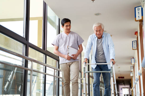 asian senior patient walking using a walker guided by physical therapist stock photo