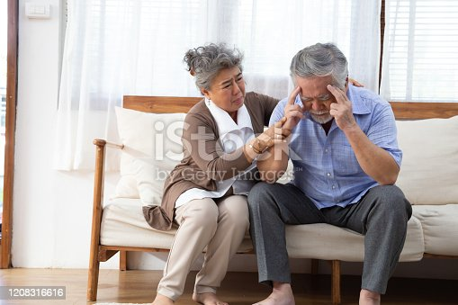 istock Asian senior retired couple holding hands and take care together at home, Alzheimer disease or suffering with dementia concept 1208316616