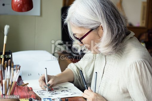 istock Asian senior woman artist sketching 544464624