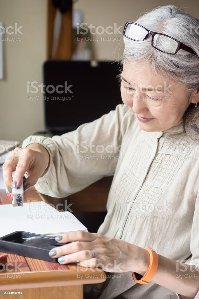 Asian senior woman artist using Suiteki and sudzuri stock photo
