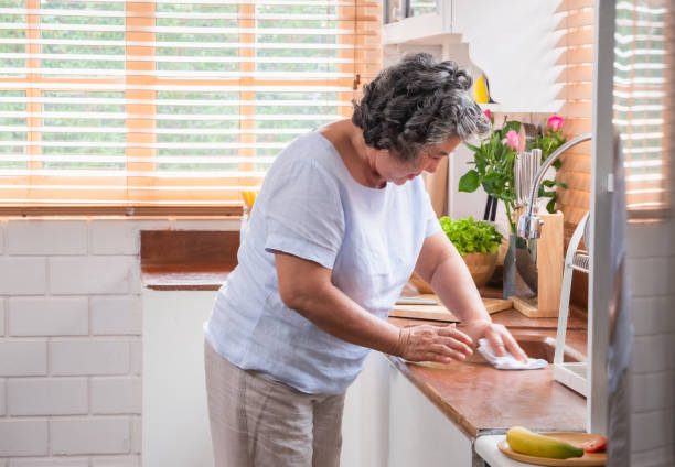 Asian senior woman cleaning a sink with rag in the kitchen ,Happy ageing at home concept stock photo