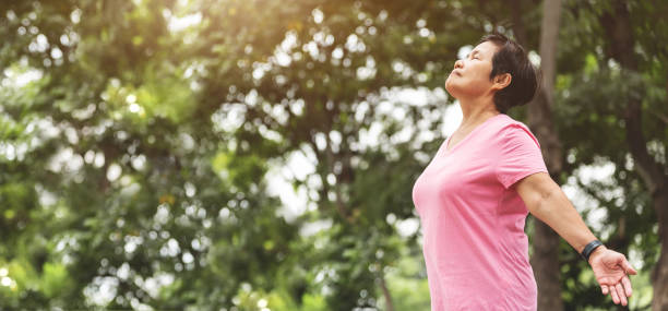 Asian senior woman in pink shirt breathing fresh air at the park while exercising. stock photo