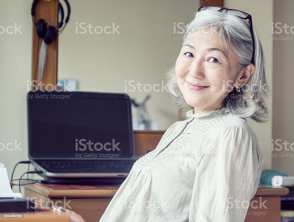 Asian senior woman leaned back in her chair and smiling stock photo
