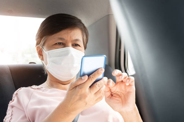 Asian senior woman Passenger wear surgical mask for prevent coronavirus or Covid-19 using smartphone while sitting in car. stock photo