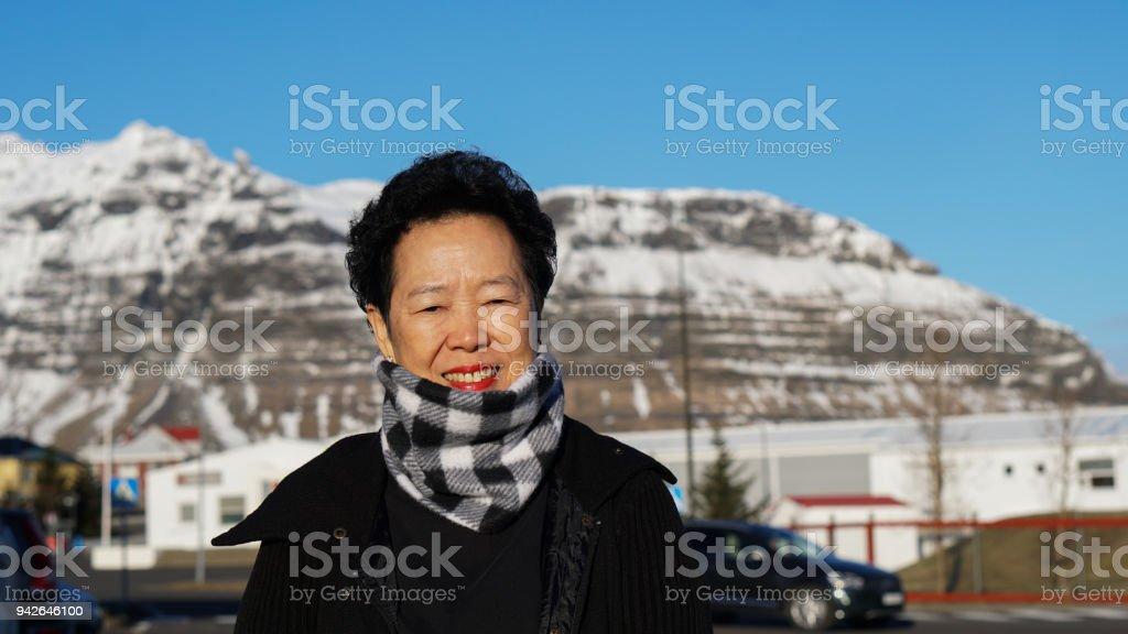 Asian senior woman portrait in Europe mountain village moring sun stock photo