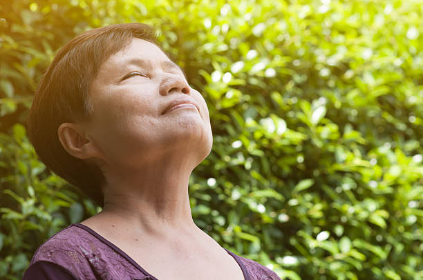 Asian senior woman relaxing and breathing fresh air. - Photo