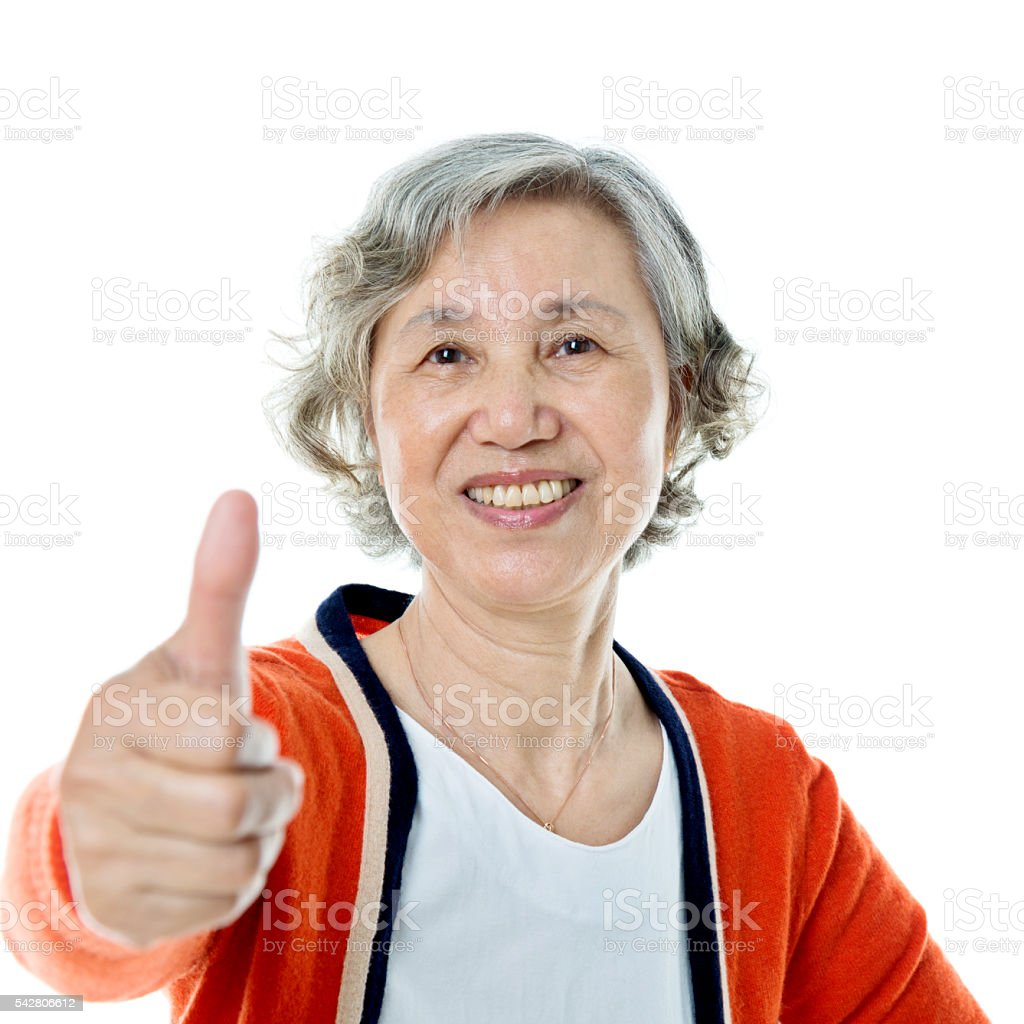 Asian senior woman showing thumbs up sign stock photo