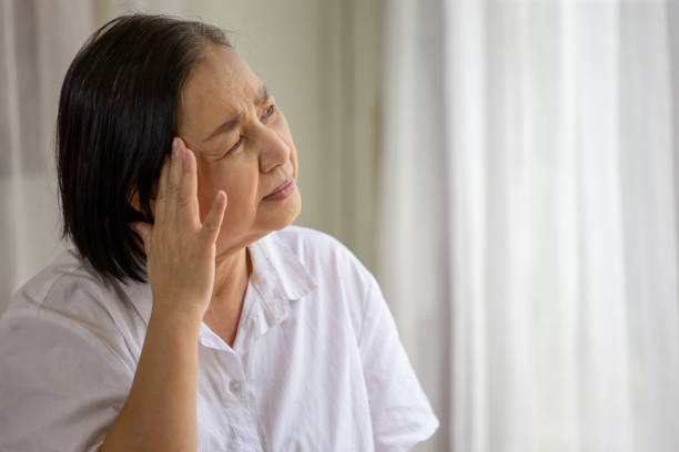 Asian senior woman sitting on sofa having headache at home. old female   stressed dizzy . elderly touching her head with her hands while having migraine or alzheimer .memory loss . indoor. copy space stock photo