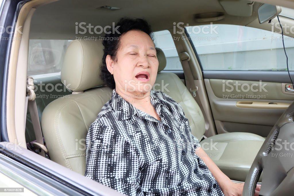 Asian Senior woman sleeping in car stock photo