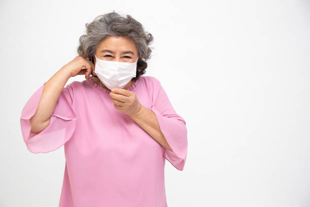 Asian senior woman wearing a protective face mask for plague coronavirus or covid-19 infectious disease. Facial hygienic mask for safety outdoor environmental awareness or virus spread concept Asian senior woman wearing a protective face mask for plague coronavirus or covid-19 infectious disease. Facial hygienic mask for safety outdoor environmental awareness or virus spread concept deathly stock pictures, royalty-free photos & images