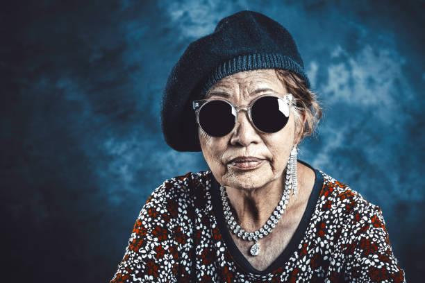 asiatiska senior kvinna som bär svarta solglasögon - celebrities of age bildbanksfoton och bilder