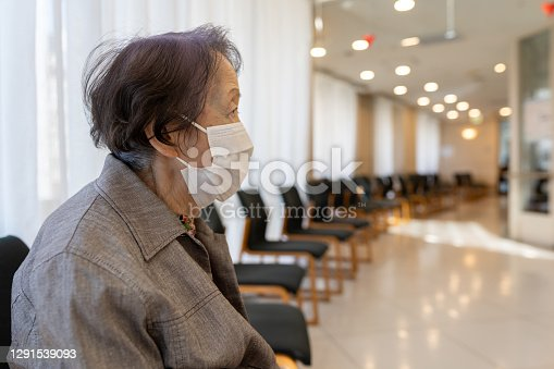 Japanese senior woman wearing face mask in a hospital, empty waiting room.