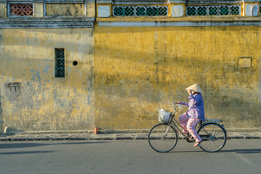 Asian senior woman with conical hat, riding bike on street