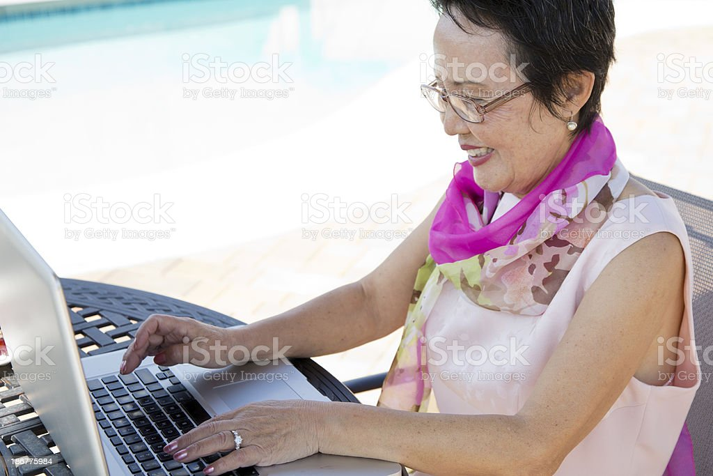Asian Senior Woman Working on Laptop stock photo