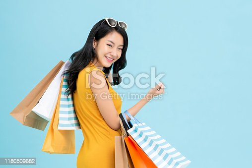 Beautiful shopaholic Asian woman carrying shopping bags in light blue background with copy space for sale and discount concepts