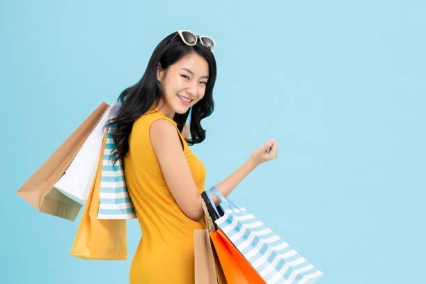 mulher shopaholic asiática que carreg sacos de compra coloridos - lifestyle color background - fotografias e filmes do acervo