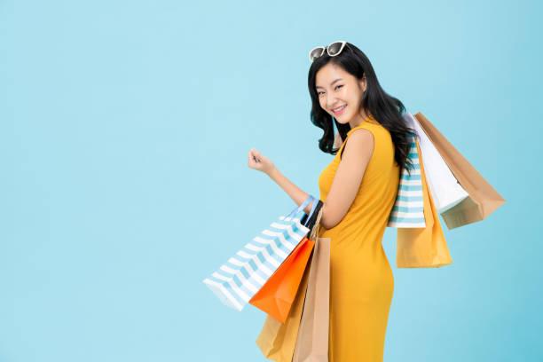 Asian shopaholic woman carrying colorful shopping bags stock photo