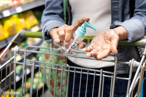 Asian shopper disinfecting hands with sanitizer in supermarket during shopping for groceries