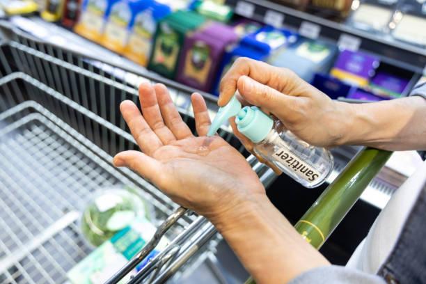 Asiatische Käufer desinfizieren Hände mit Desinfektionsmittel im Supermarkt beim Einkaufen – Foto