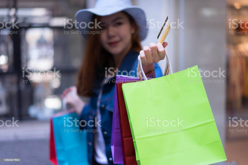Asian shopping woman holding credit or debit card and shopping bags...