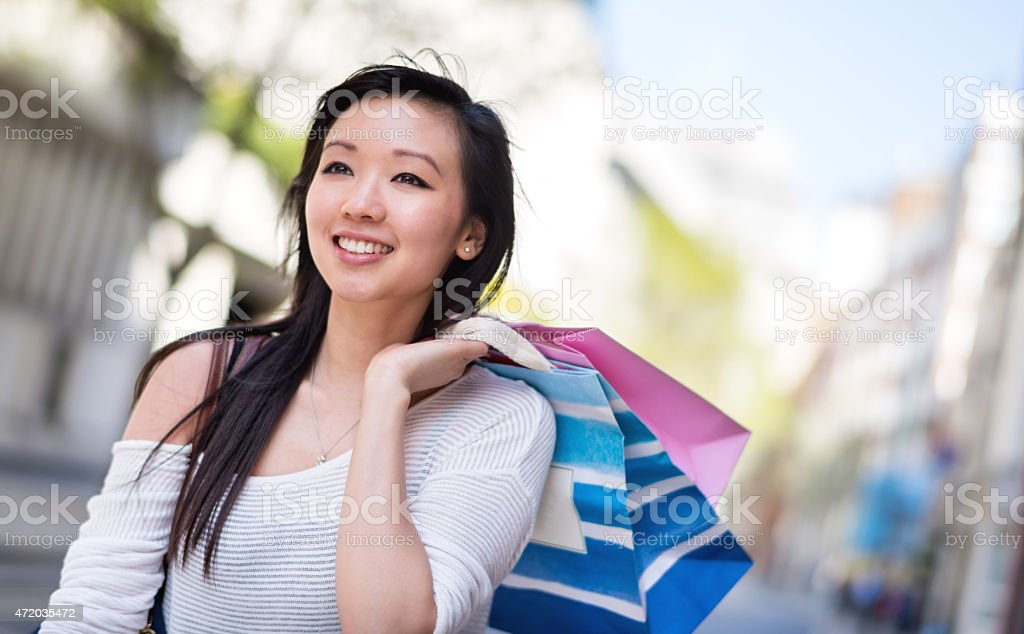 Asian shopping woman walking on the street holding bags